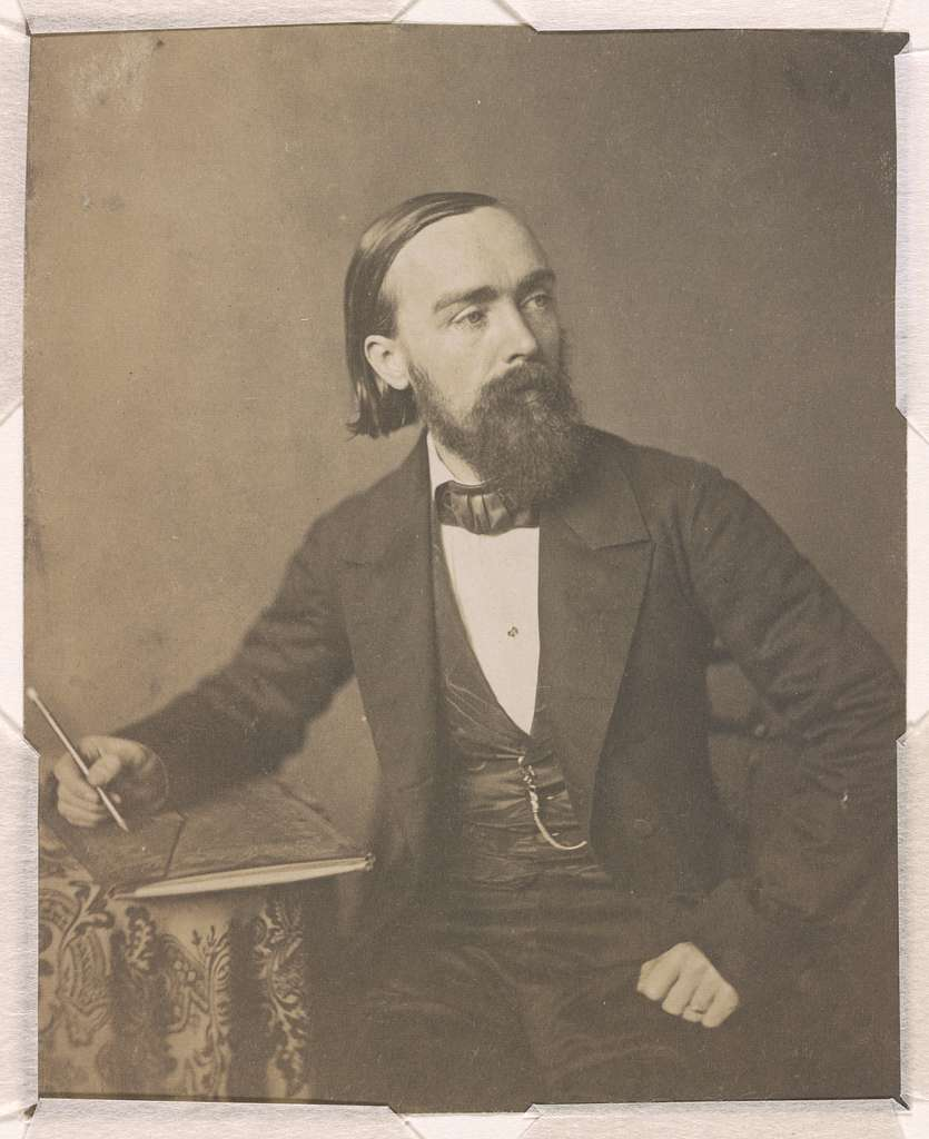 Paul Weber, artist, three-quarter length studio portrait, seated, holding pencil in right hand on sheaf of paper on a table, facing right