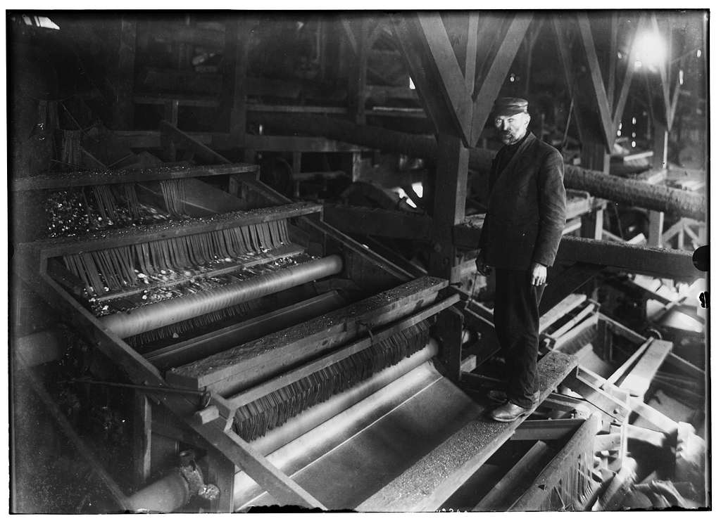 Mr. A. Langerfeld and one of his machines for picking coal which does away completely with the use of breaker boys. The percent of slate that goes in with the coal separated by this machine is 1% to 2%, where the percent with the old primitive method of using boys is from 15% to 60%. This picture was taken at the breaker of the Spencer Coal Co., at Scranton, Pa., on March, 18, 1913. Location: Scranton, Pennsylvania