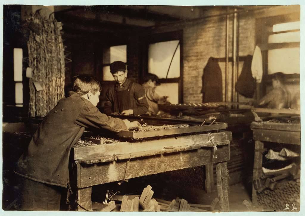 """Boys """"linking"""" bed-springs. 14 and 15 years old. Location: Boston, Massachusetts Lewis W. Hine"""