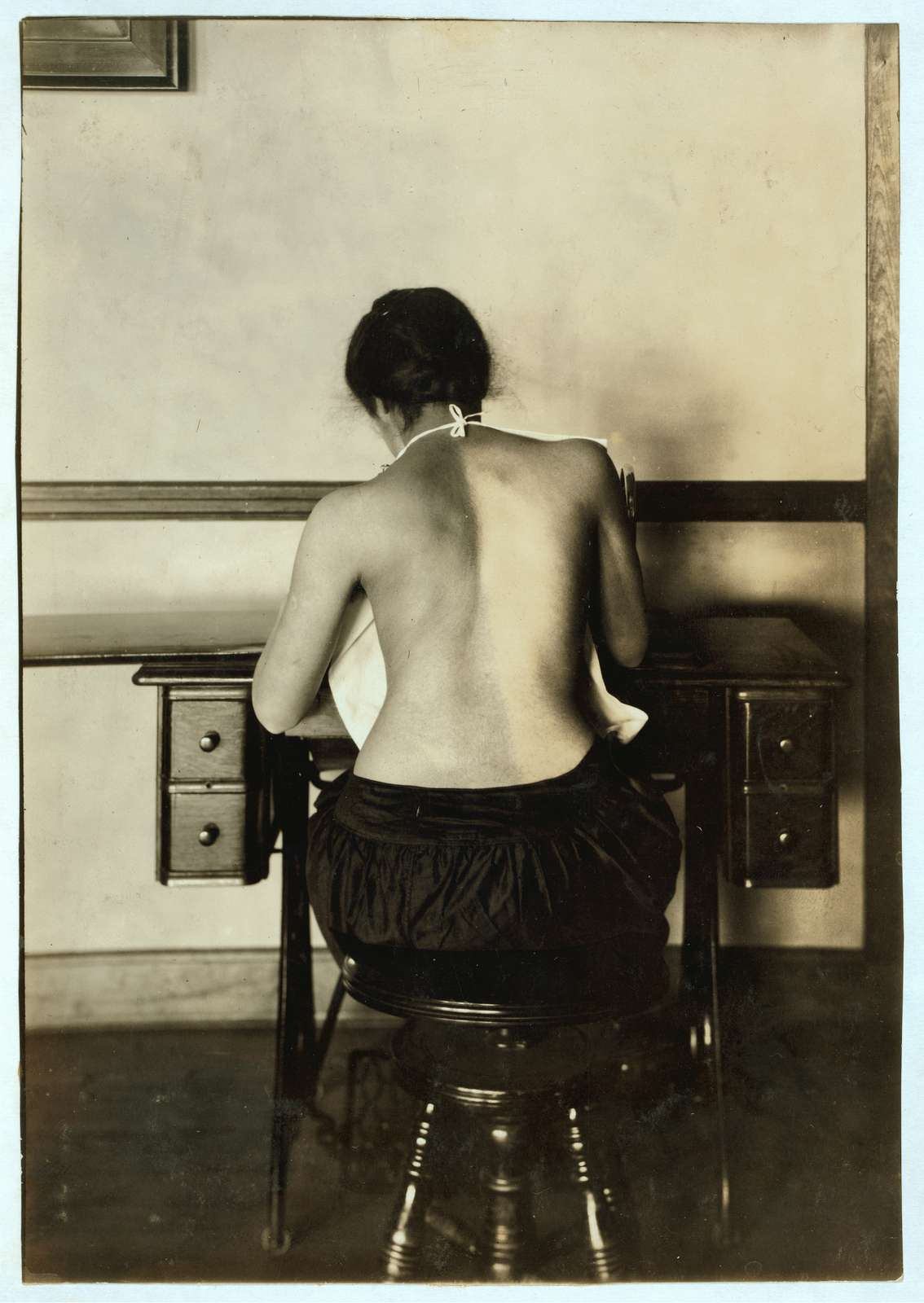 Mildred Benjamin, 17 years old. Right dorsal curvature. Scoliosis. Right shoulder higher than left. Shows incorrect position required to perform this kind of work. Stopping use of right arm. See 4667, 4671 & 4672. Location: Boston, Massachusetts Lewis W. Hine