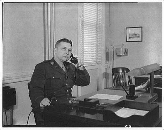 Charlotte Hall Military Academy. Uniformed man at desk, using phone