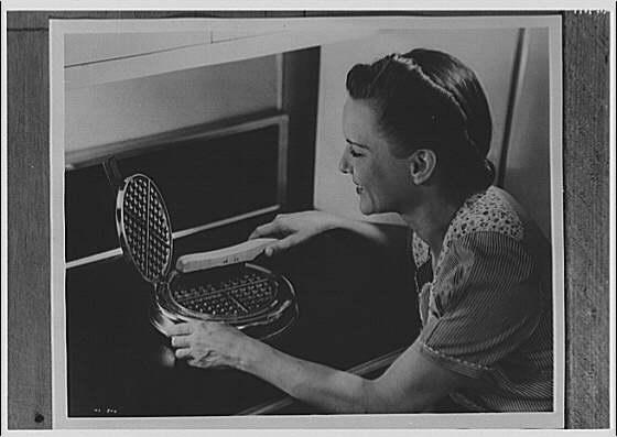 Electric Institute of Washington. Woman cleaning waffle iron