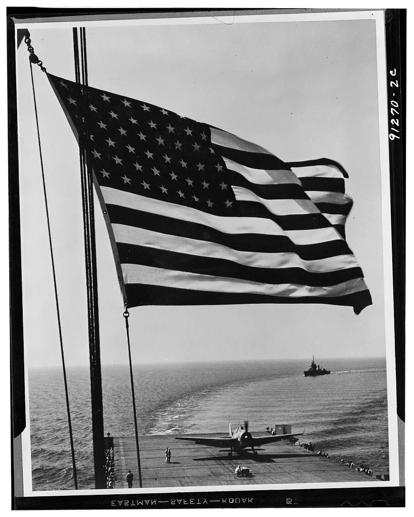 Airplane landing on flight deck of aircraft carrier with American flag in foreground