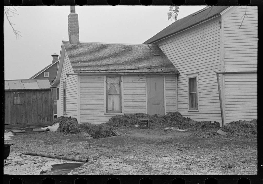 Part of house on Russell Natterstad farm showing necessity for banking foundation with manure. The cellarway is also filled with manure