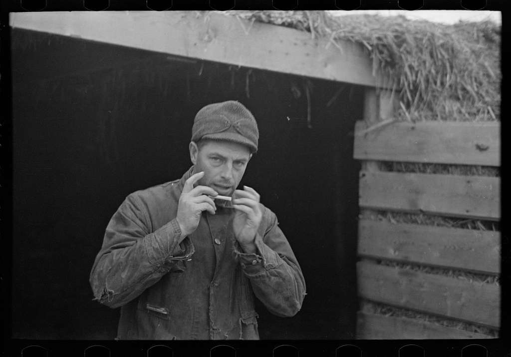 "Rex Inman, farmer, near Estherville, Iowa, rolling a cigarette. Very few farmers smoke ""tailor mades"""