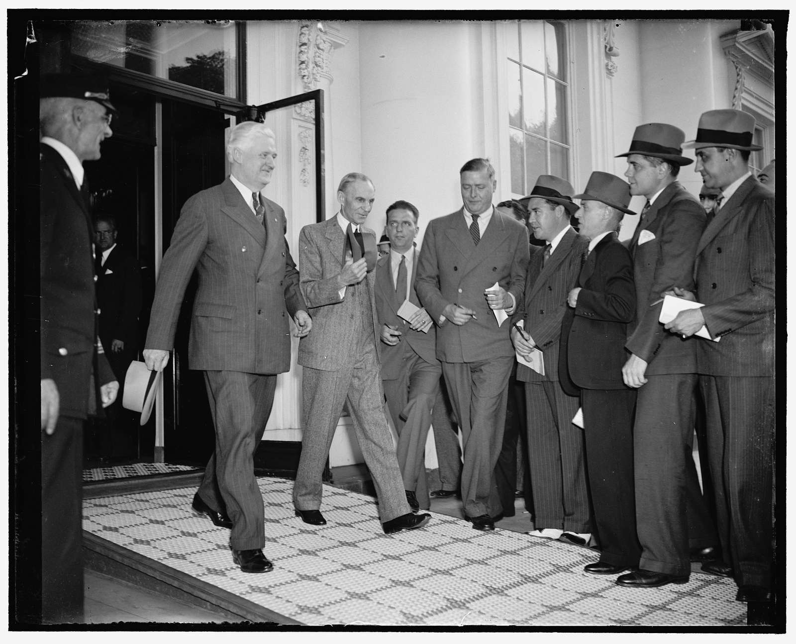 Auto magnate leaves White House after conference with President Roosevelt. Washington, D.C., April 27. Forced to run a gantlet of newspaper reporters, Henry Ford is pictured leaving the White House today with Maj. Henry M. Cunningham, Manager of the Alexandria, VA.O branch of the Ford Motor Co., after a luncheon and conference with Presdient Roosevelt. Both the White House and Ford refused to make a statement following the discussion which lasted a couple of hours, 42738