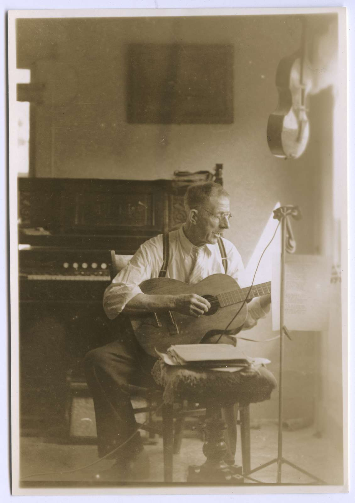 George Vinton Graham with guitar, seated, right profile, looking downwards, portrait, photograph