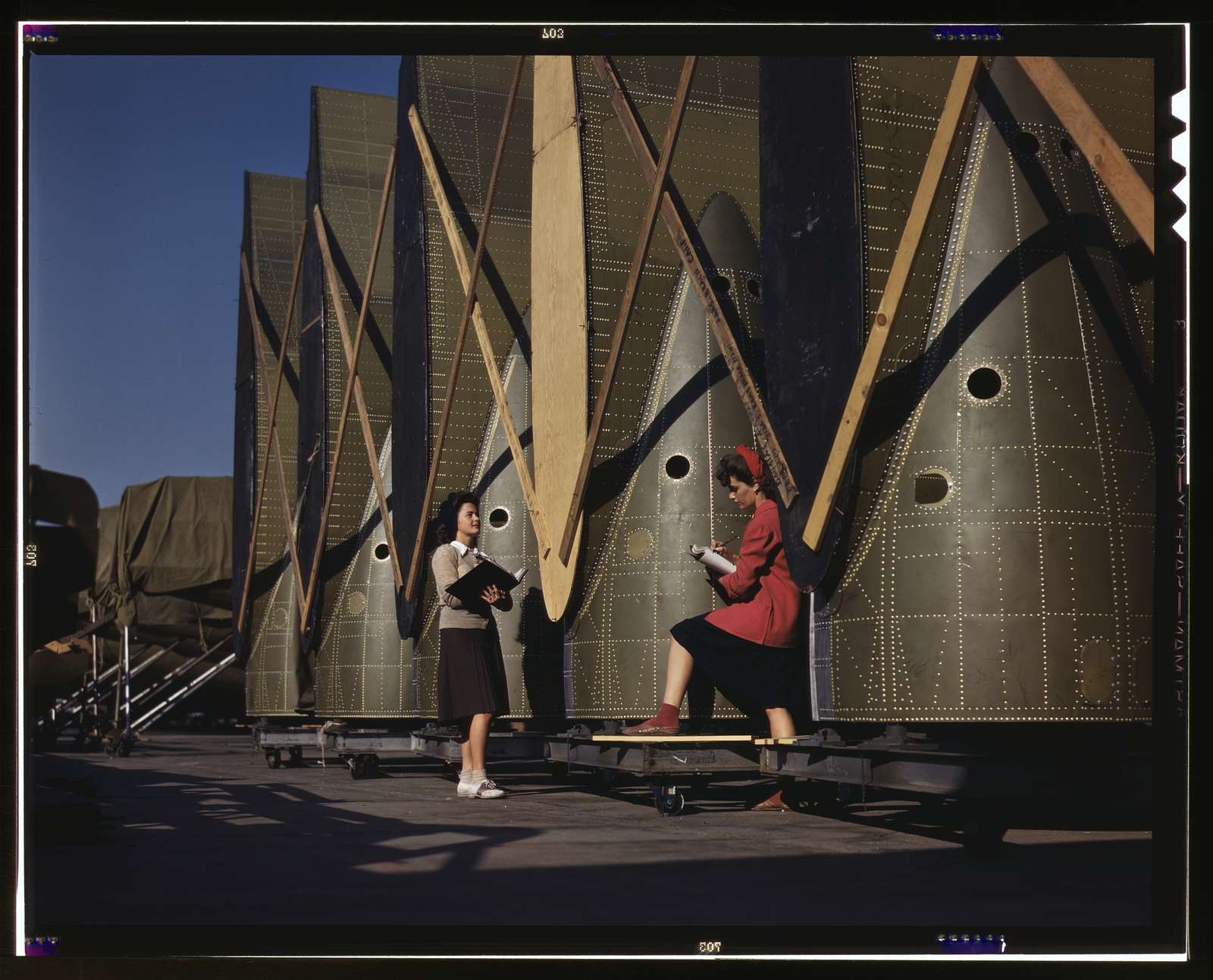 Carefully trained women inspectors check and inspect cargo transport innerwings before they are assembled on the fuselage, Douglas Aircraft Company, Long Beach, Calif