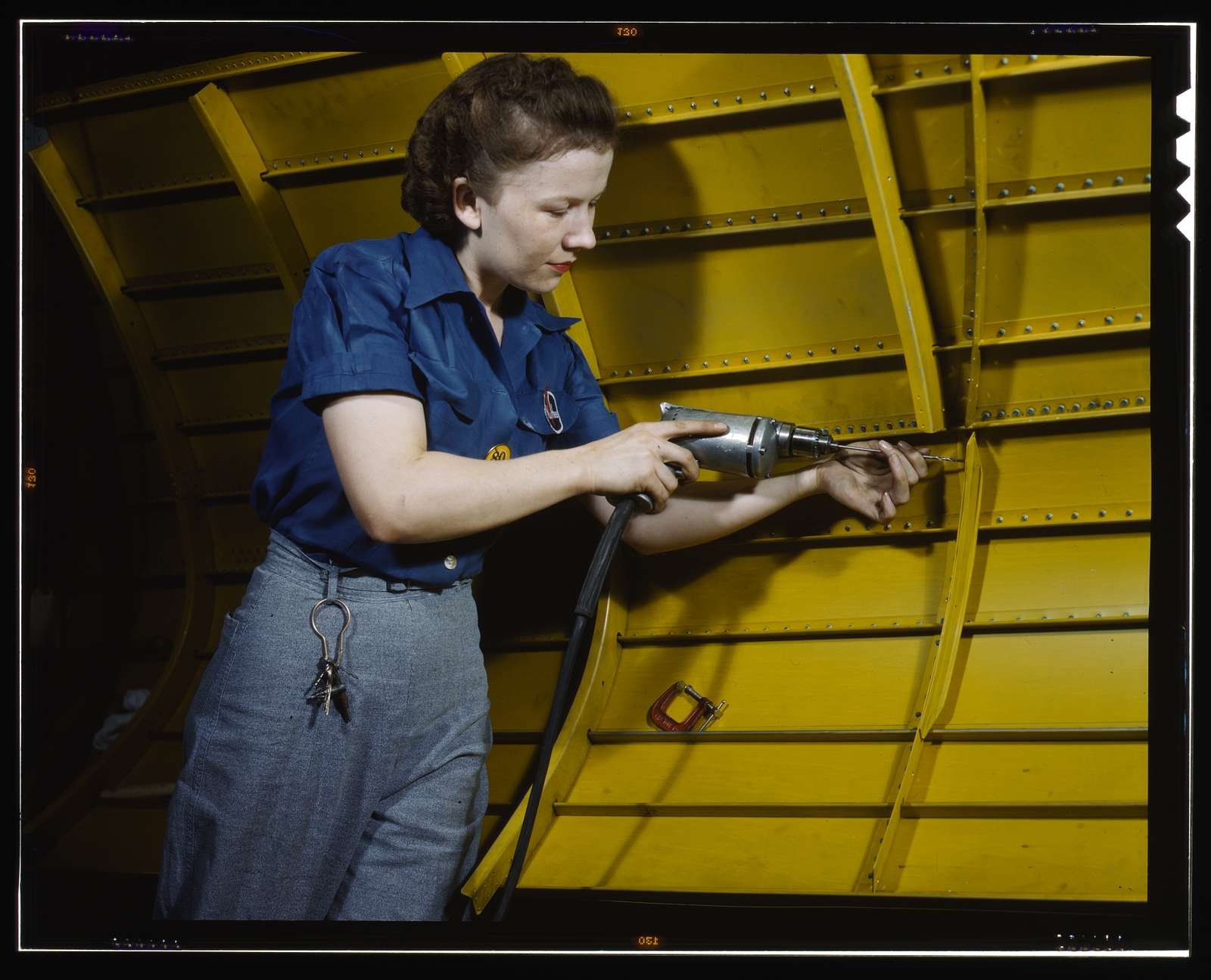"""Operating a hand drill at Vultee-Nashville, woman is working on a """"Vengeance"""" dive bomber, Tennessee"""