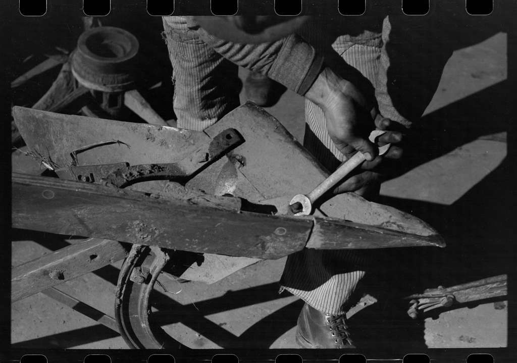 Untitled photo, possibly related to: Blacksmith's helper disassembling plow belonging to Pomp Hall, Negro tenant farmer from Creek County, Oklahoma. Blacksmith shop is in Depew, Oklahoma. See general caption number 23