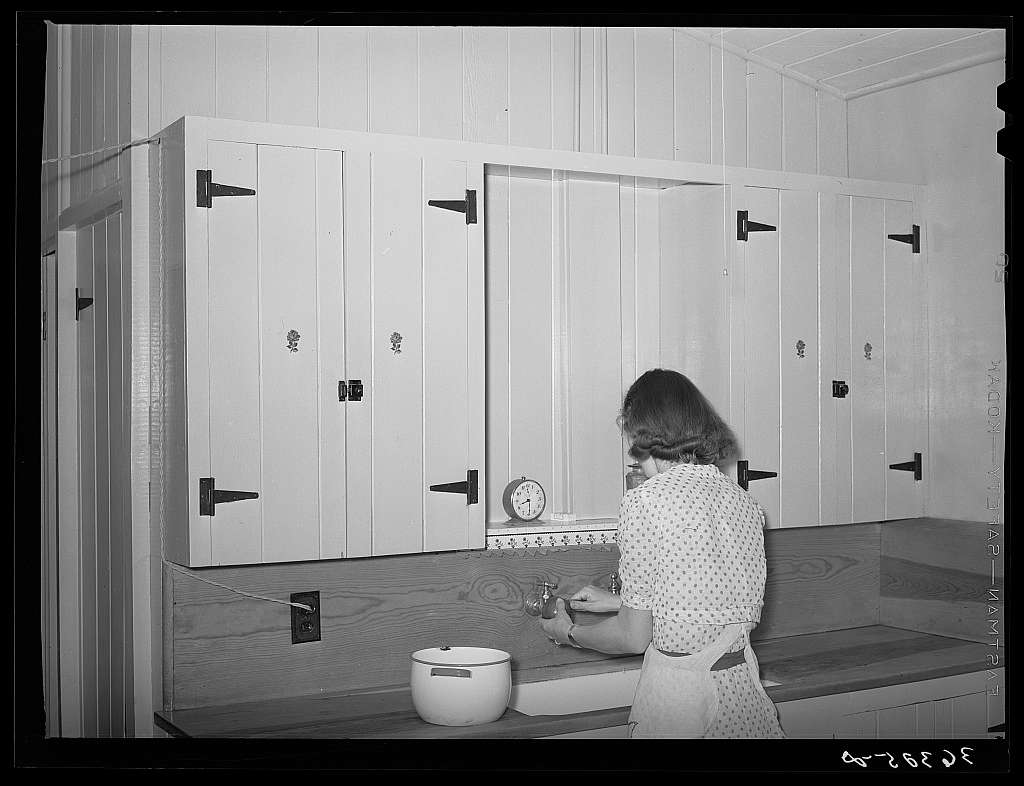 Wife of member of the Casa Grande Farms working at her kitchen sink. Pinal County, Arizona