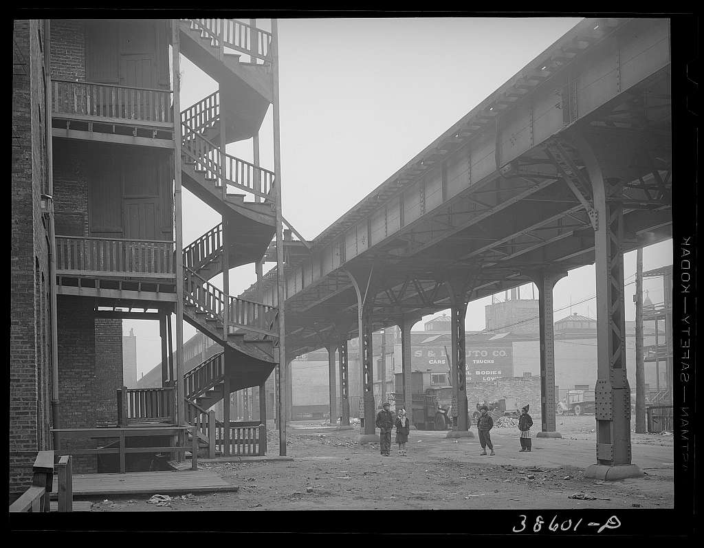 Children playing under the elevated on the southside of Chicago, Illinois