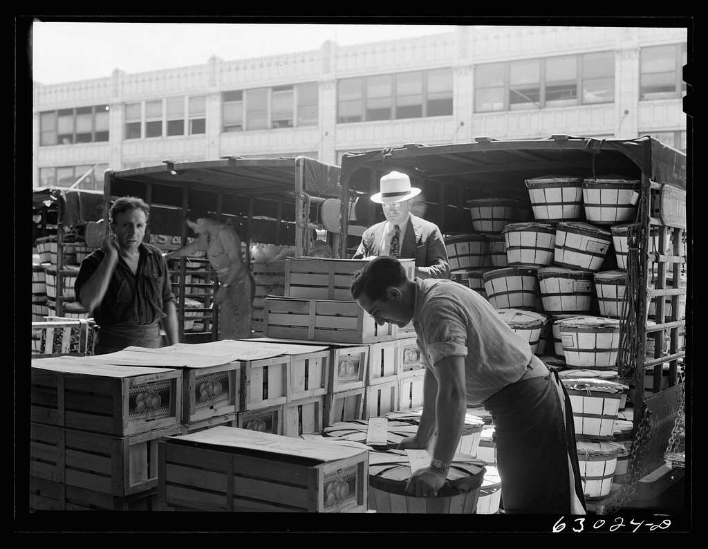 Commission merchant supervising unloading of truck at produce market. Chicago, Illinois