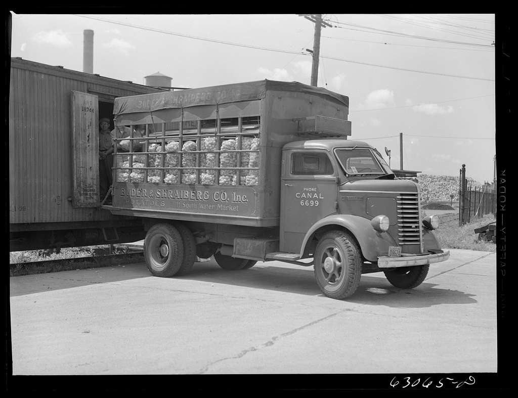 Loading potatoes onto truck from freight car. Chicago, Illinois