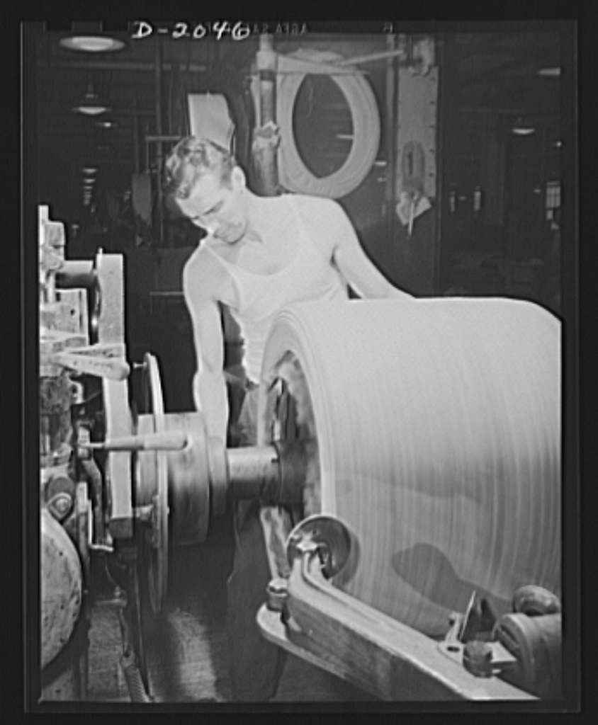 """Shaping the tire with """"saucers."""" Spinning discs which are delicately controlled by movable arms smooth out each layer of fabric as it is added to the growing carcass, and curves around the sidewall and bead with considerable pressure. In the center foreground, one of these saucers may be seen as this tire builder maneuvers it around the sharp corner of the tire drum. In the right foreground two others pull across from the center to the edges to smooth out each layer. Firestone (General Tires), Akron, Ohio"""