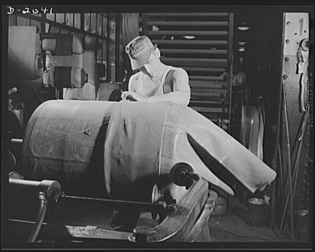 Tire building. This tire builder starts the carcass by slipping a layer of fabric onto the tire drum. The layer is made with the seam cut on the bias so that there will be no straight-across strain on the tire seams. The layer fits tightly, and each successive layer is banded to the preceding one by applied pressure. Firestone (General Tires), Akron, Ohio