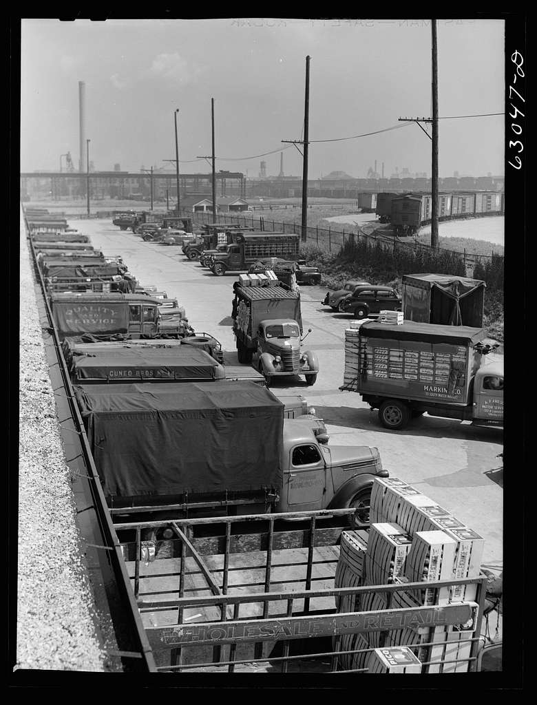 Trucks of commission merchants lined up outside fruit terminal to haul produce market what has been bought at auction. Chicago, Illinois