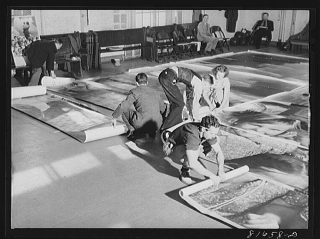 Washington, D.C. Preparing the defense bond sales photomural, to be installed in the Grand Central terminal, New York, in the visual unit of the FSA (Farm Security Administration). Laying out finished prints for inspection