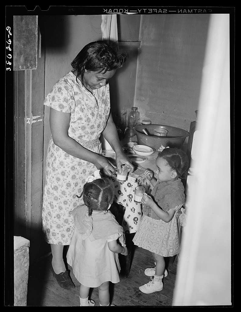 Wife of railroad worker feeding her children. Chicago, Illinois