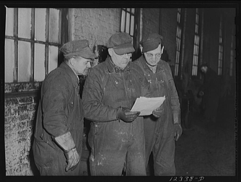 Chicago, Illinois. Foreman discussing a job with two workmen at a Chicago and Northwestern Railroad yard