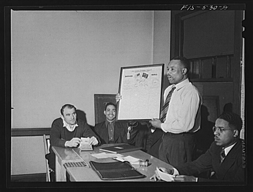 Chicago, Illinois. Good Shepherd Community Center. President of a steelworkers union local displaying honor roll on which names of members going into the armed forces will be listed
