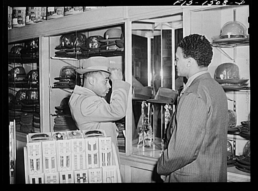 Chicago, Illinois. Mr. Claude Walker trying on a new hat in the Henry C. Taylor Store For Men, 47th Street near State. The salesman is Mr. William Strong, who is manager of the store