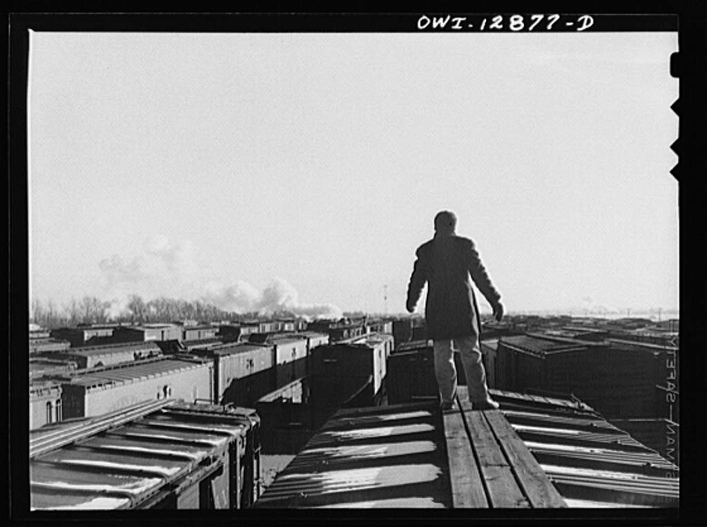 Chicago, Illinois. Switchman riding a car at a Chicago and Northwestern Railroad yard
