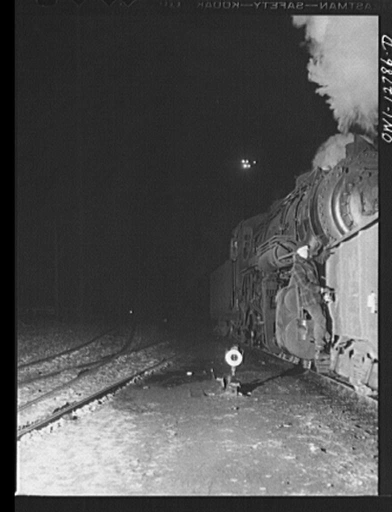 Chicago, Illinois. Switchman riding a car in one of the Chicago and Northwestern Railroad classification yards