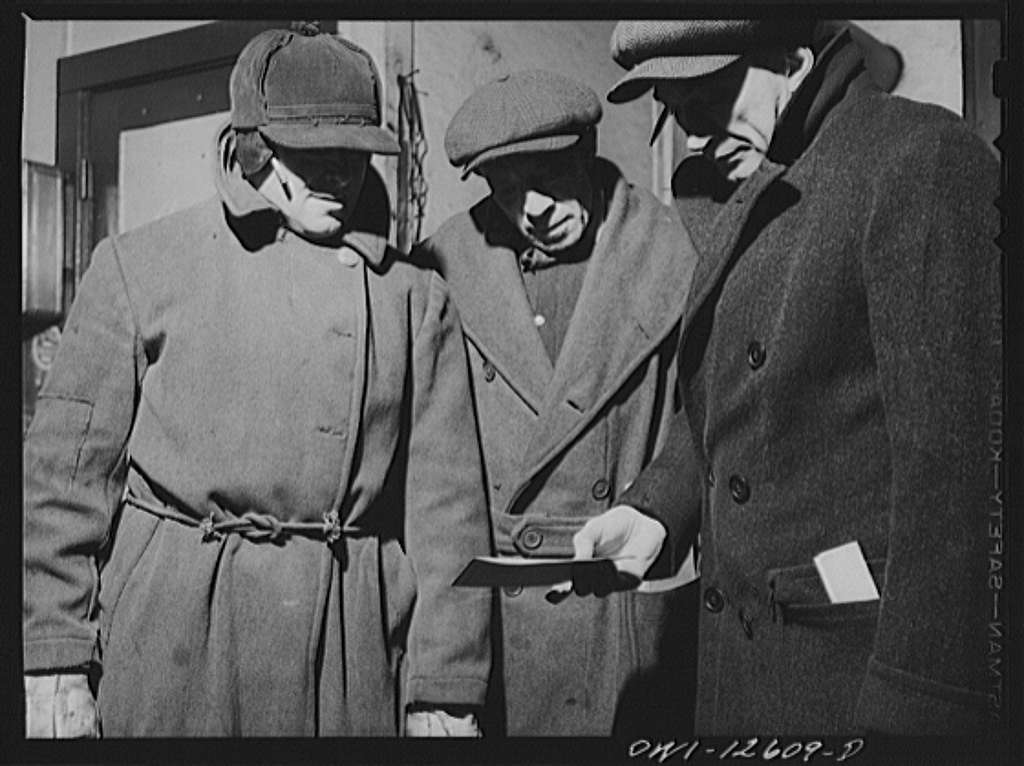 Chicago, Illinois. Yardmaster (right) going over the list of a train with two switchmen at a yard of the Chicago and Northwestern Railroad