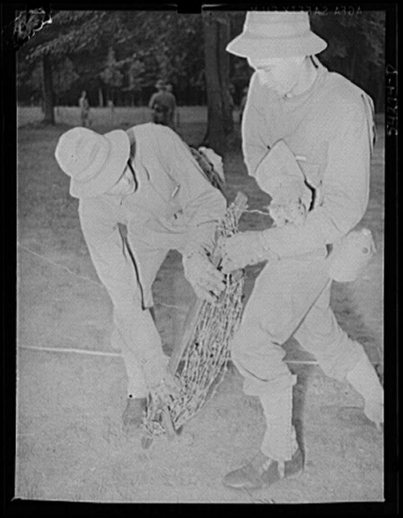 Fort Belvoir, Virginia. Two soldiers, wearing heavy gloves, handling barbed wire steel screw type picket