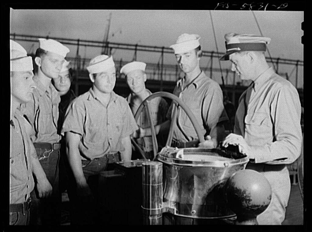 Hoffman Island, merchant marine training center off Staten Island, New York. Mr. Stone instructing trainees in piloting at the wheel of the schooner Vema