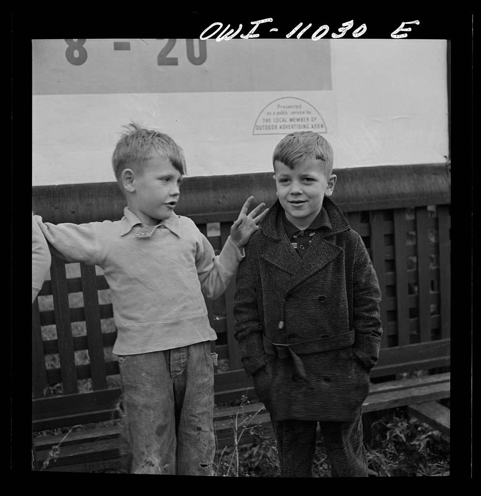 Lititz (vicinity), Pennsylvania. Boys playing near a billboard. Most of their fathers work in nearby defense plants