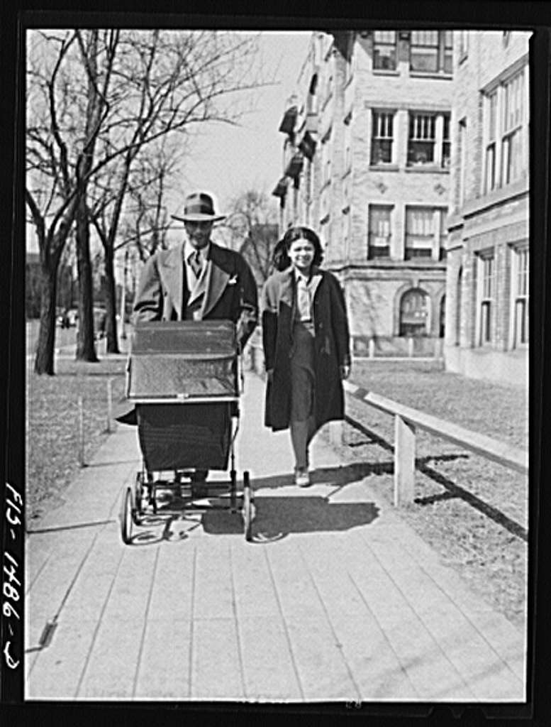 Mr. and Mrs. Oliver Coleman taking their five-month-old son out for some air along Indiana Avenue. Chicago, Illinois