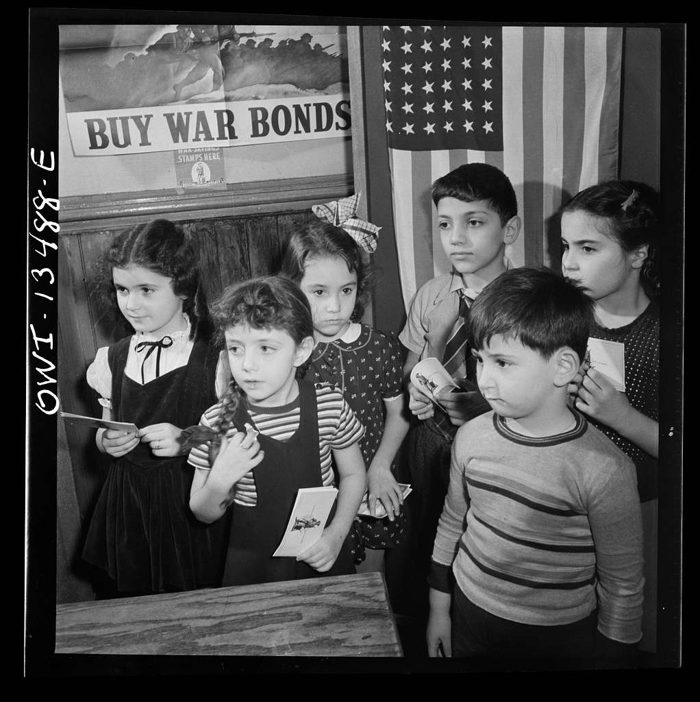 New York, New York. Children waiting in line to buy defense stamps at public school from mothers who volunteer to guard doorways and perform other duties in schools under the school defense aid program