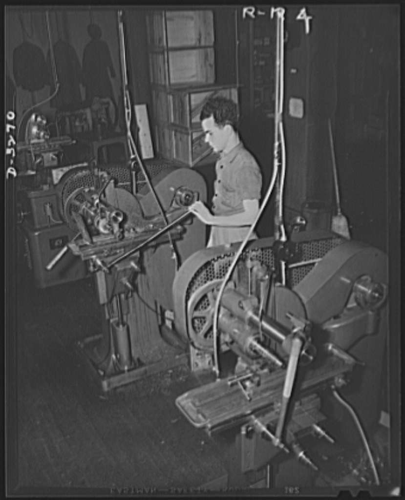 Oil burners to machine gun parts. With conversion of a New York State oil-burner plant to production of precision parts for machine guns, additional equipment and manpower were mandatory. Unable to purchase sufficient new machines, these two used to hand operated milling machines were installed. The young worker was recruited from a defense vocational training school. Reif-Rexoil Company, Buffalo, New York