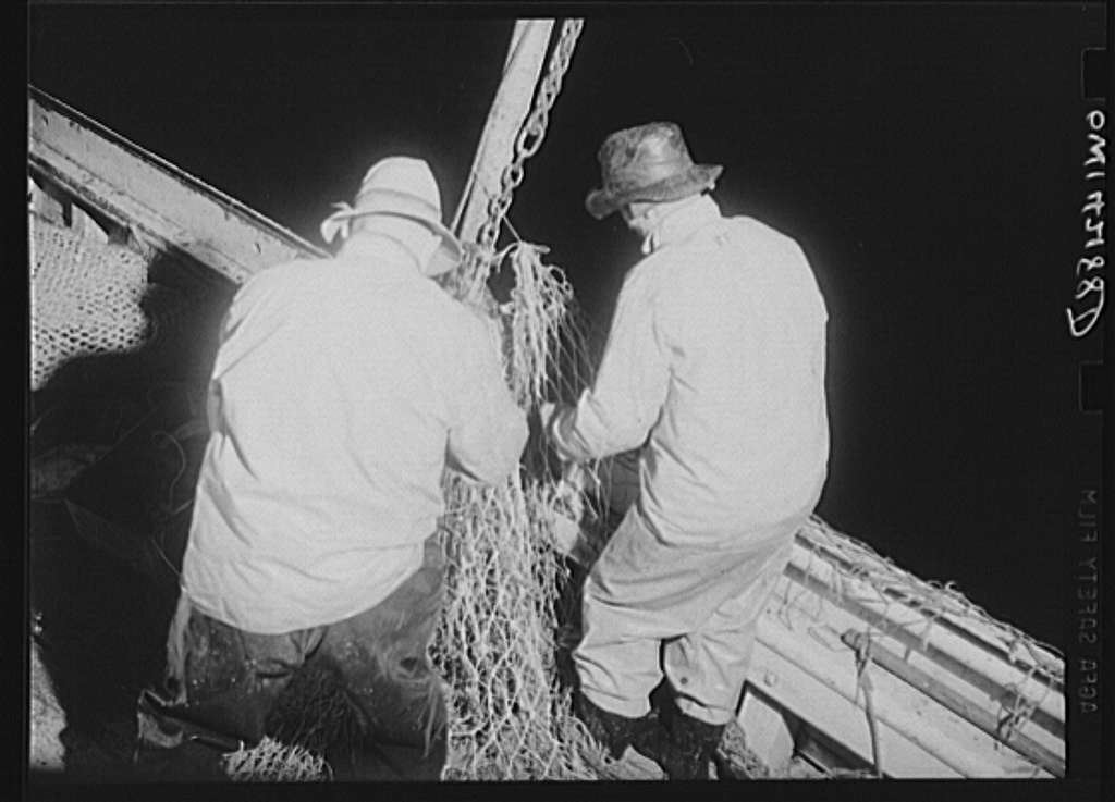 On board a fishing vessel out from Gloucester, Massachusetts. Two fishermen mending a badly torn net during the night