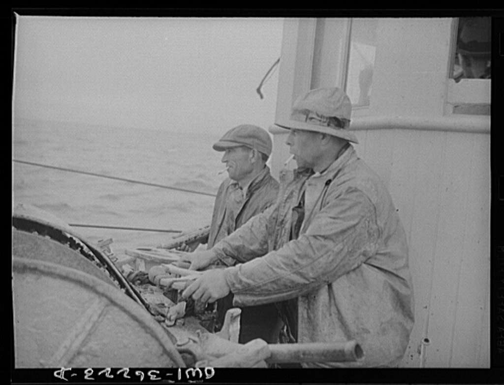 On board a fishing vessel out from Gloucester, Massachusetts. Winch control men intent on seeing to it that the proper amount of cable is let out at the proper spot