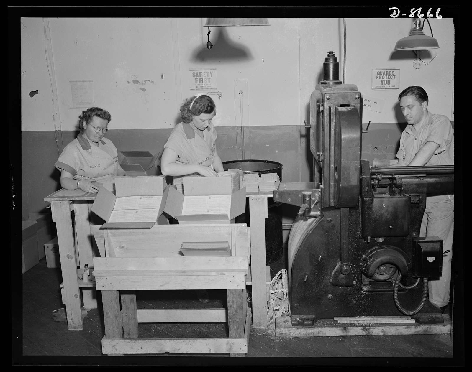 Printing war ration book 2. Glued sheets containing four ration books pass through the cutting machine and come out into single ration books. Weelan Reilly feeds the cutter as Ida Stuart, left, and Isabel Small, check the books and pack them in cardboard containers