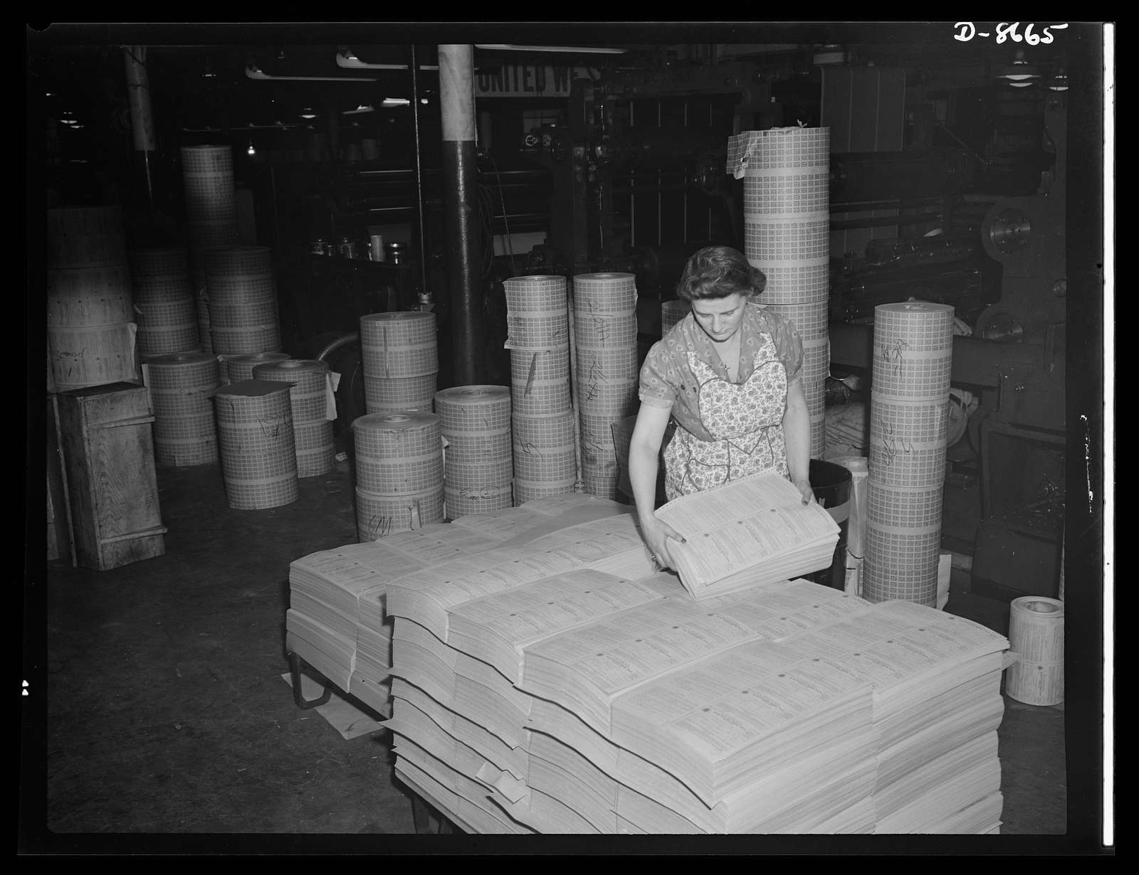 Printing war ration book 2. Jessie Calabase stacks the sheets containing four coupon books as they come from the collator ready to be transferred to the cutting department