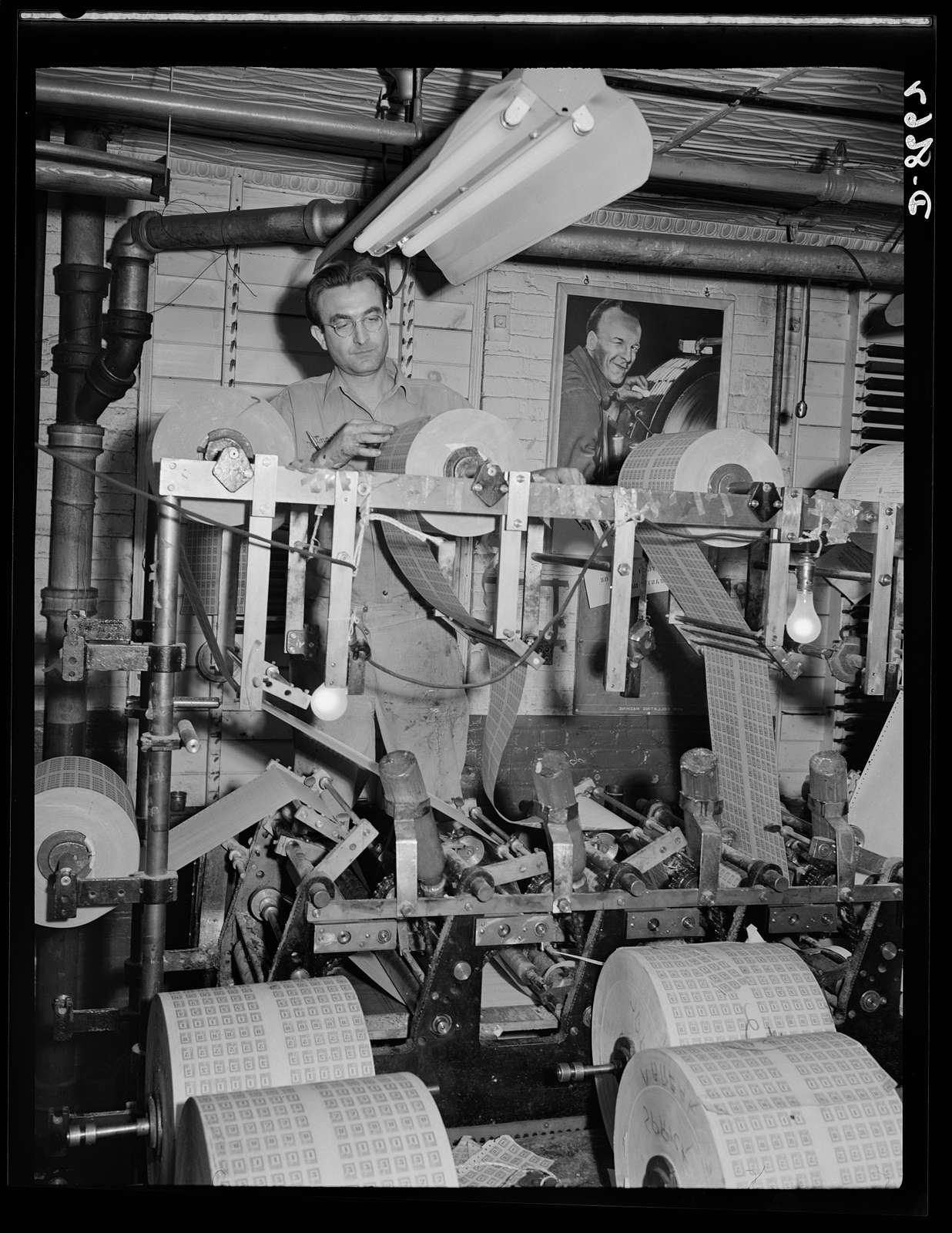 Printing war ration book 2. The coupons and covers flow through the collator where the pages and covers are assembled and glued. The coupons and covers leave the collator assembled in glued sheets aggregating four war ration books. Otto Krants inspects a roll of coupons on collator