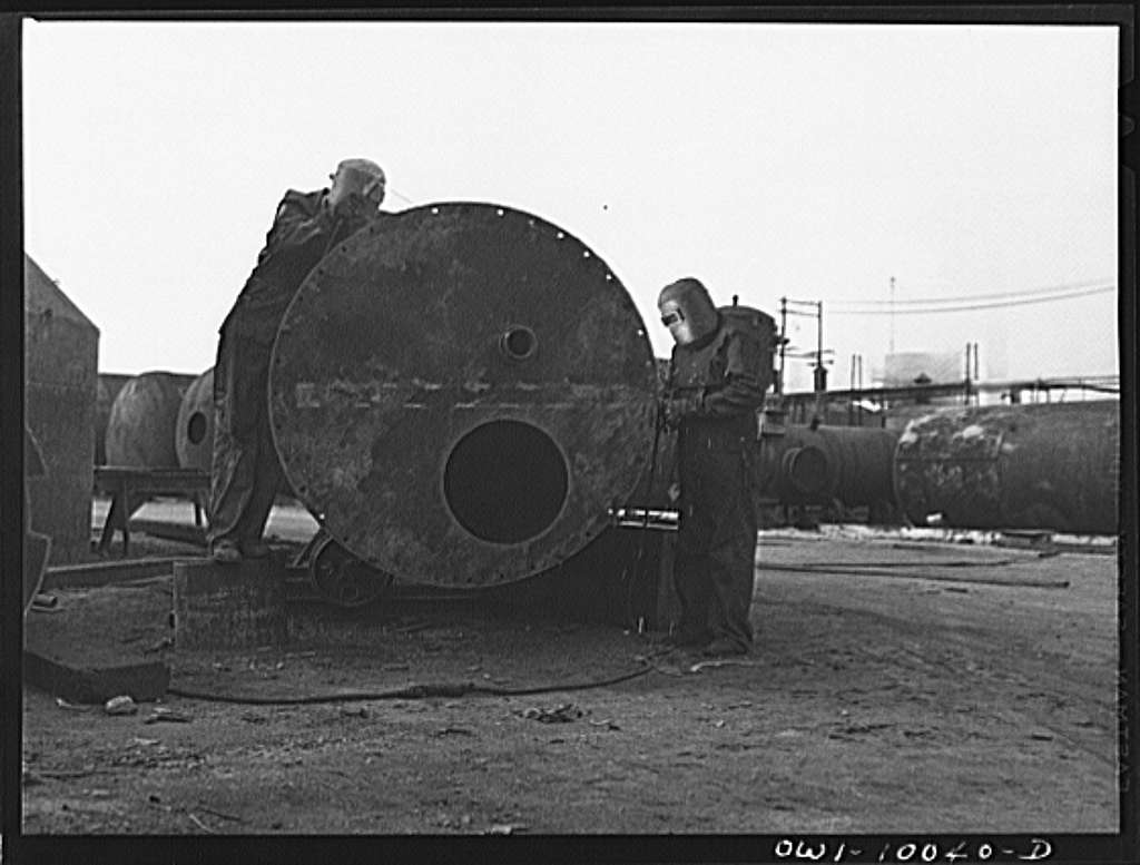 Tulsa, Oklahoma. Welders at work on a tank being made from salvaged material at the Mid-continent refinery