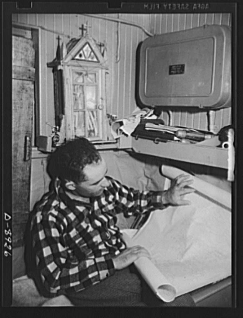 Victory food from American waters. Captain John Riberia, on the fishing trawler Old Glory, checks a sea chart in his cabin. His catch will be rosefish, a variety many housewives will substitute for canned sardines, salmon and mackerel, which are needed for the armed forces