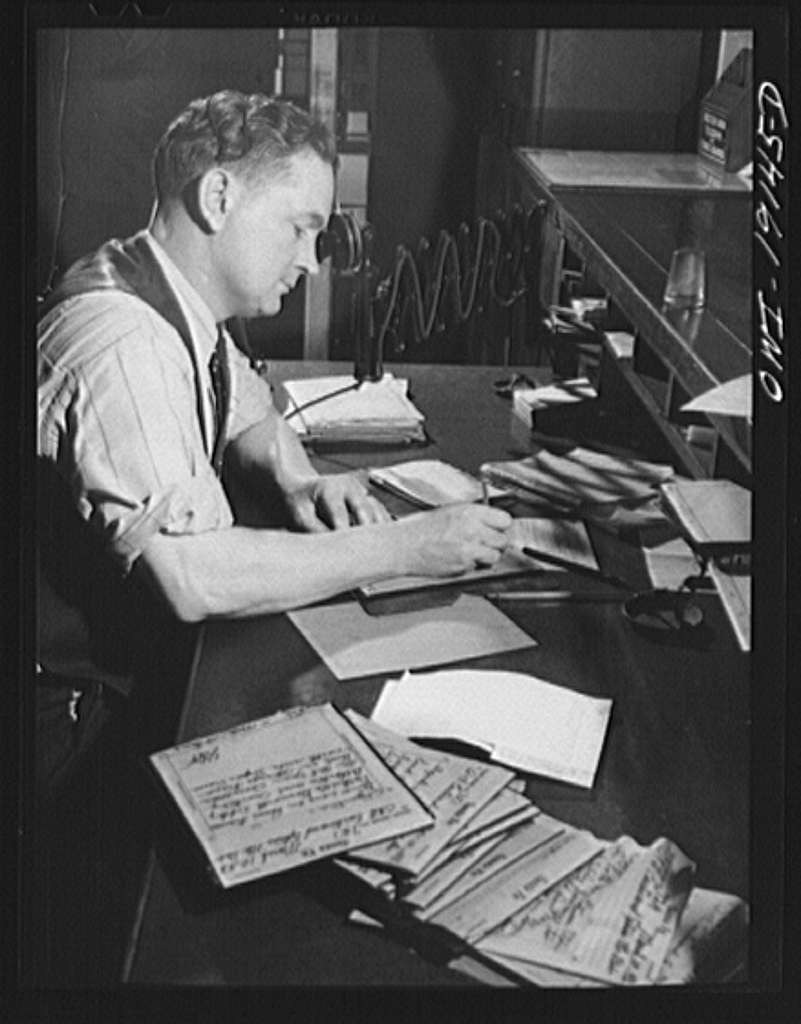 Argentine, near Kansas City, Kansas. Writing train orders in the telegraph room of the Atchison, Topeka and Santa Fe Railroad offices