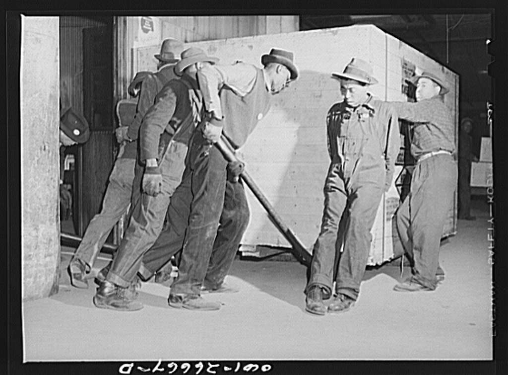 Chicago, Illinois. Freight handlers moving a very heavy piece of freight at the United States Army consolidating station