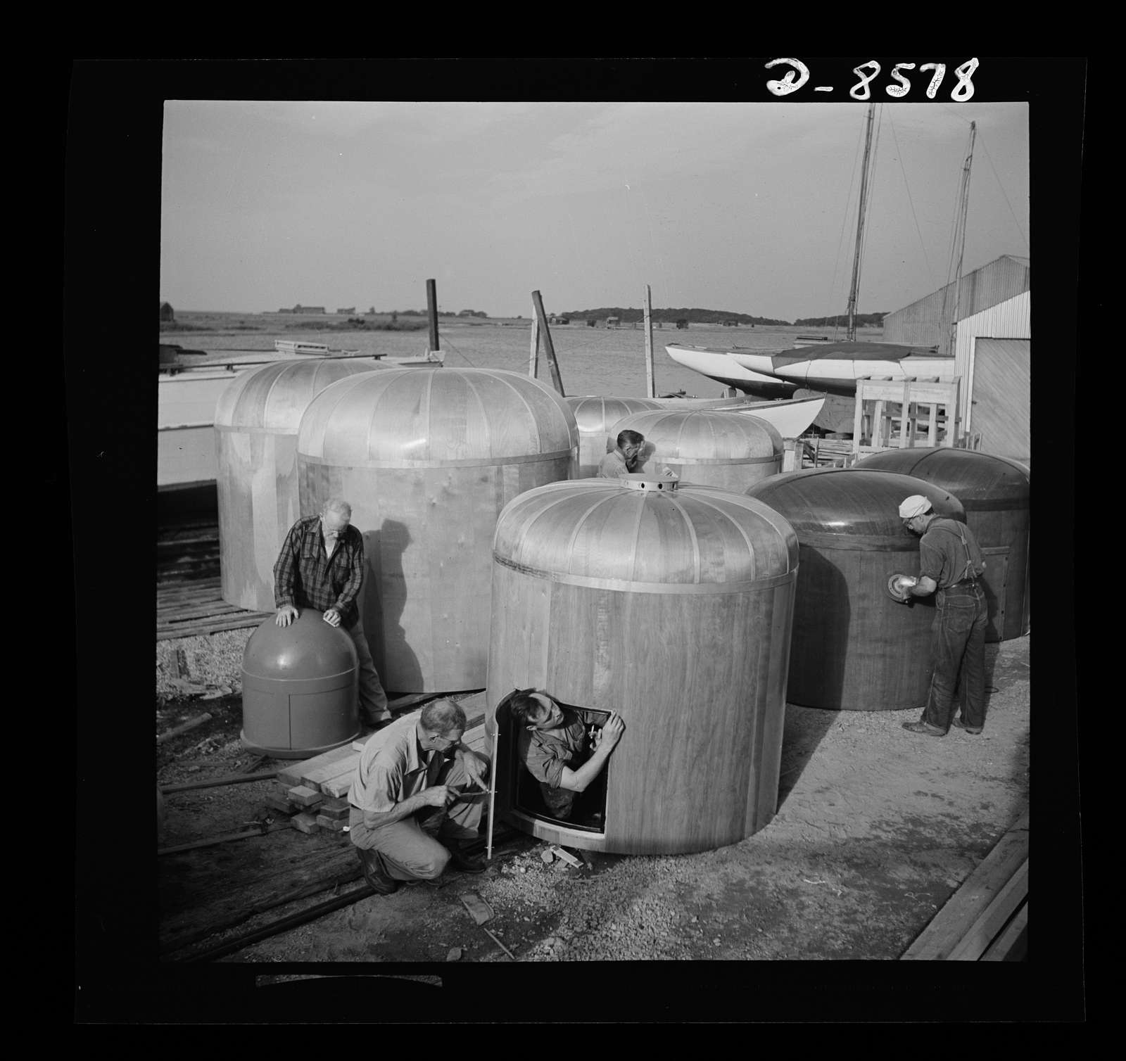 Conversion. Rowing shells to life rafts. Though they look like satin cushions, these smoothly sanded instrument protectors are made from plywood. Exact purpose of the covers is a military secret. Workers in the foreground are fitting the door on a completed protector