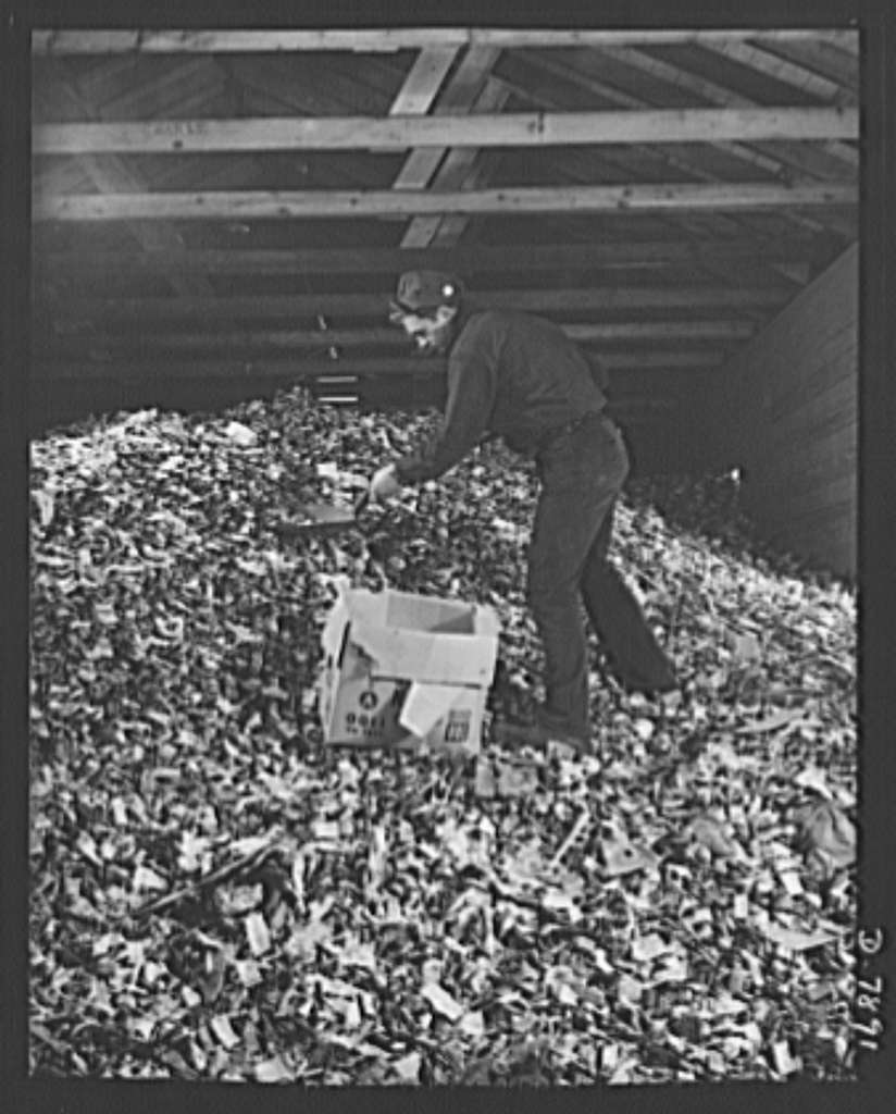 Empty collapsible tubes: a tin mine for war industry. Some of the millions of old tooth paste, shaving cream and other metal tubes received at the Newark, New Jersey reclamation plant of the Tin Salvage Institute. Frank Thomas, age 19, works at the trimming of the huge pile of squeezed-out tubes