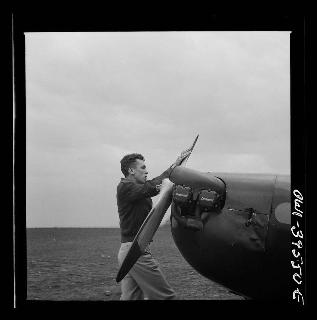 Frederick, Maryland. Walter Spangenberg, a student at Woodrow Wilson High School, spinning the propeller for a fellow student at the Stevens Airport