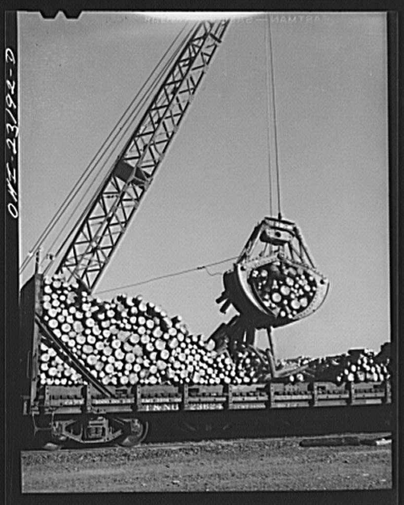 Lufkin, Texas. Southland paper mill. Crane unloading flat car of pulpwood in the wood yard