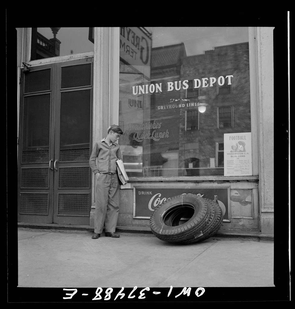 Washington Court House, Ohio. A schoolboy, who rides to and from school daily on a Greyhound bus, waiting outside the depot