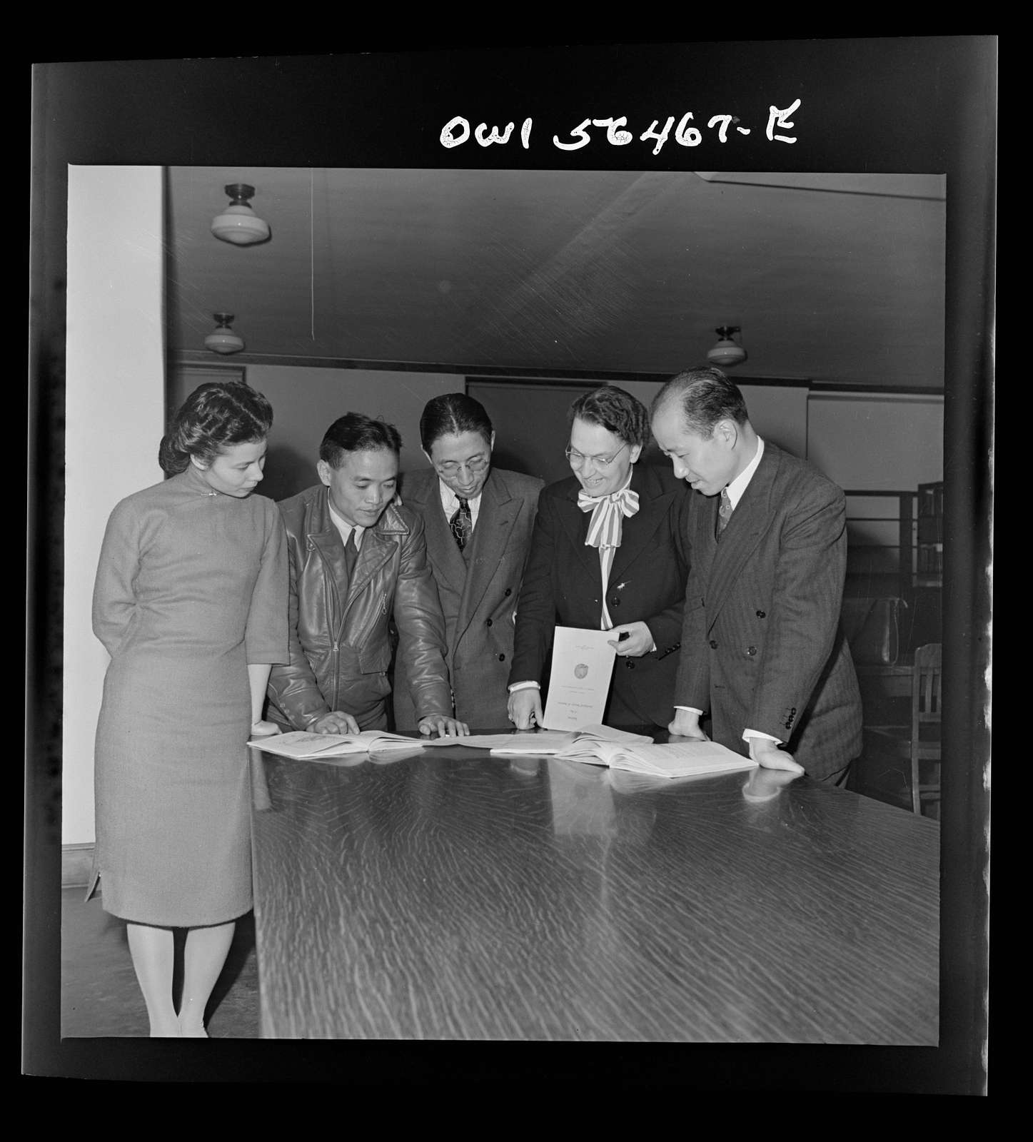 Chinese technical experts inspect reference material in University of Maryland library where they were taking courses offered by the UNRRA (United Nations Relief and Rehabilitation Administration) training center. From left: Miss Ing (from Far Eastern Division, UNRRA Washington office); H.W. Li; .P.C. Chao; Miss Eleanor Hindler (special consultatnt, ILO office, Montreal, who is acting as coordinator of the course for Chinese technical experts at UNRRA training center); and C.C. Yeh